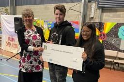 EPA Tasmania's Maree Bakker presenting a big cheque to two students at Huonville High